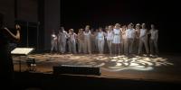 Le chœur sur scène, la chef de chœur à gauche face à la scène