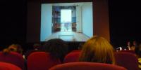 Vue du fond, un montage photographique à l'écran, une intervenante est assise d'un coté de l'estrade