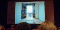 Vue depuis le fond d'une salle de cinéma, à l'écran, une photographie