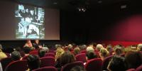 Vue depuis le fond de l'amphithéâtre du Jeu de Paume, 2 intervenants, en projection, une image N&B