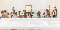 Des collégiens circulent derrière une vitrine exposant des documents manuscrits