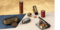 Tubes et étuis porte-louis d'or, et pièces de monnaies d'or et d'argent sur une table