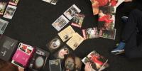 Sur une table, des revues éparpillées autour de 2 portraits en médaillon et 2 pièces d'identité