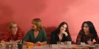 4 femmes assises à une table sur fond rouge
