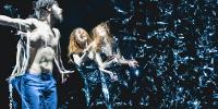 3 danseurs sur scène avec des projections de paillettes argentées