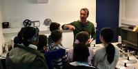 Un atelier aux Archives départementales de la Seine-Saint-Denis : un intervenant de face, 7 élèves
