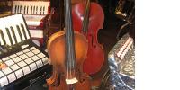 Un violon sur un socle devant un violoncelle, sur les côtés, des accordéons
