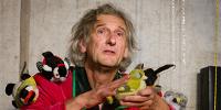 Le comédien en plan rapproché, SDF avec des oiseaux en peluche sur les épaules et dans les mains