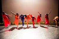 Vue du fond de la scène, les danseurs en rouge sont dos au public et penchés en avant sur une jambe