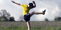 Dans une prairie de dos, une footballeuse shoote