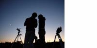2 téléscopes et 2 personnes à contrejour sur fond de crépuscule sans nuage