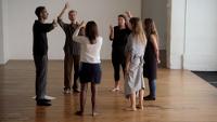 Dans une pièce vide, 6 personnes debout en cercle discutent en langage des signes