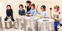 Un intervenant assis derrière 5 écoliers, dont 3 jouent de la cuíca, percussion brésilienne