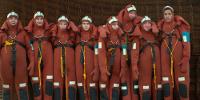 8 personnes posent en combinaison de plongée rouge du Certificat de formation de base de sécurité