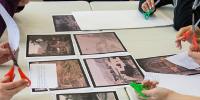 Sur une grande table, des photographies, des feuilles manuscrites, des mains avec des ciseaux