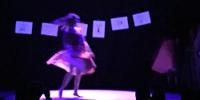 Sur scène sous une lumière bleue, une comédienne est en mouvement devant une guirlande de dessins